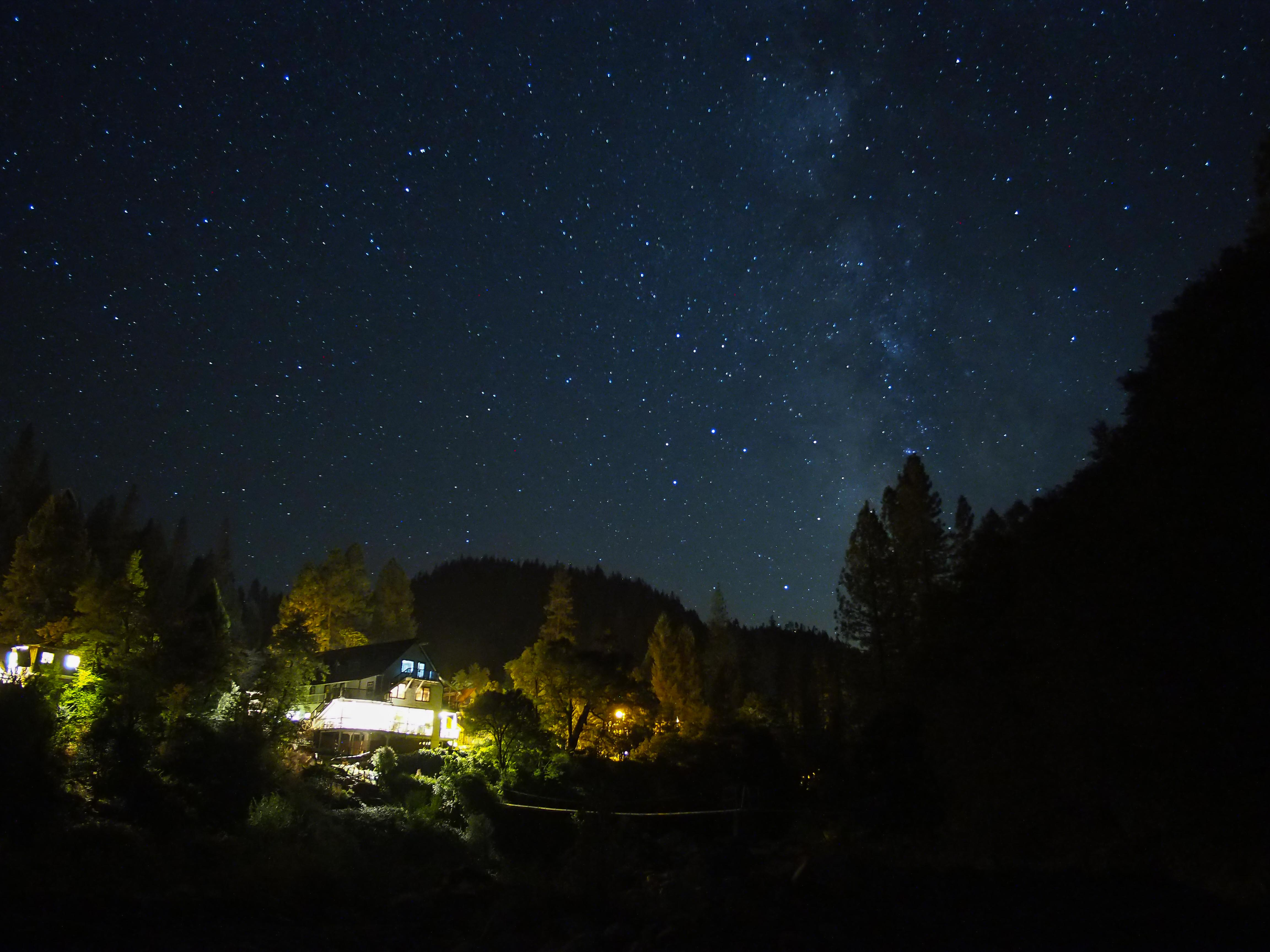 Photo of the night sky  the milky way visible above a brightly lit Washington Hotel cabin in the woods alongside the Yuba river