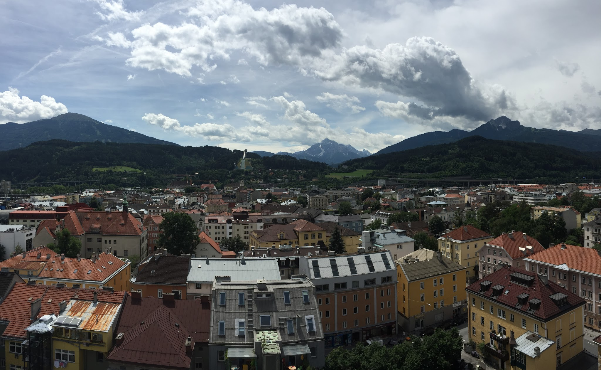 Photo overlooking Innsbruck in the foreground and the alps and partly cloudy sky in the background